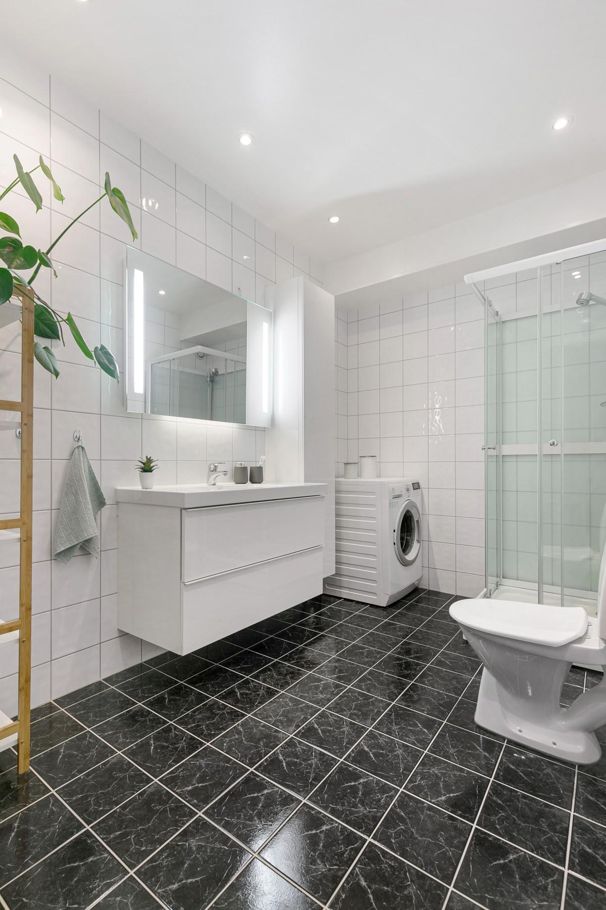 Komplett flislagt bad med god størrelse, varmekabler, opplegg for vaskemasking og spotter i tak