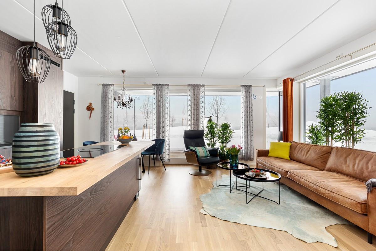 Åpen stue- og kjøkkenløsning, med store vindusflater og parken rett utfor