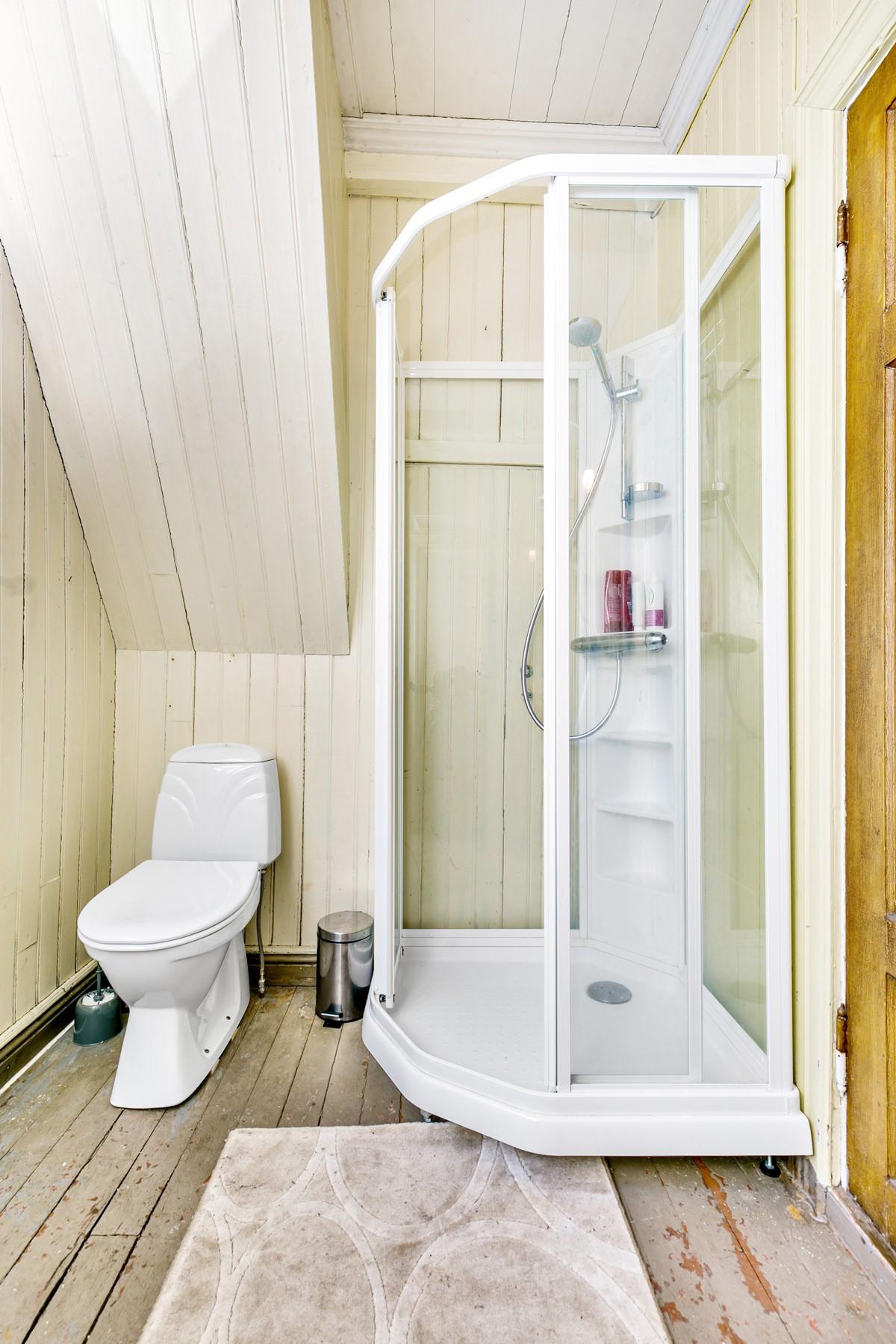 Baderommet inneholder wc, dusjkabinett og servant