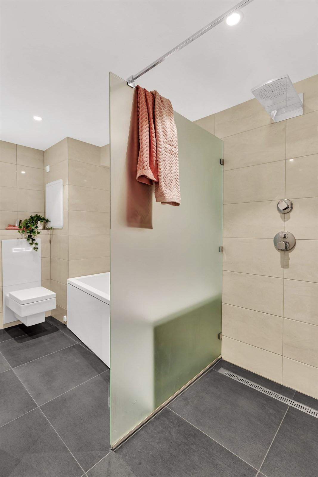 Storformat fliser på gulv; stor dusjnise og badekar