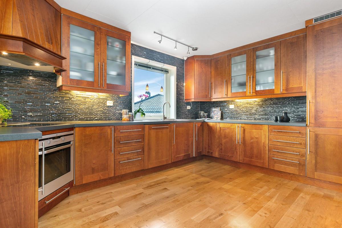 Meget romslig kjøkken innredet med beisede fronter i tre og integrerte hvitevarer