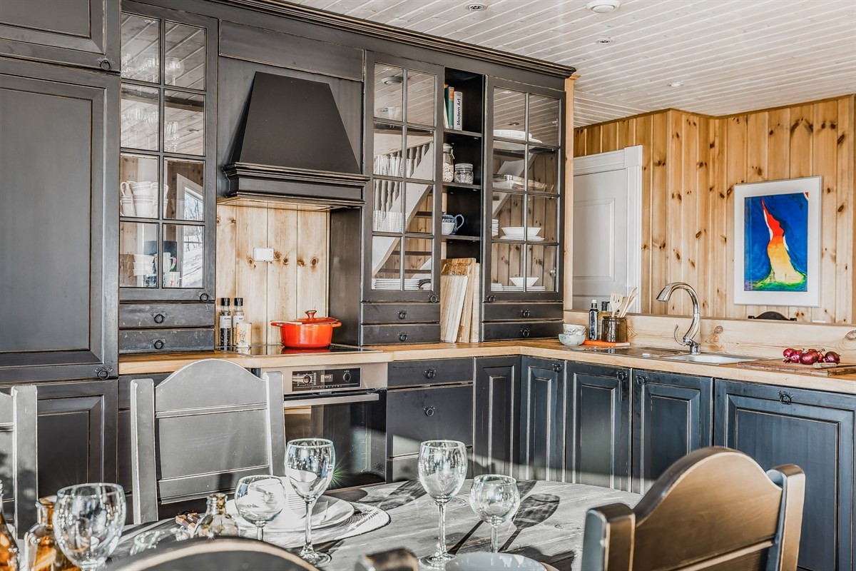 Kjøkkenet er holdt i tradisjonell hyttestil med rikelig med oppbevaring i skap og skuffer