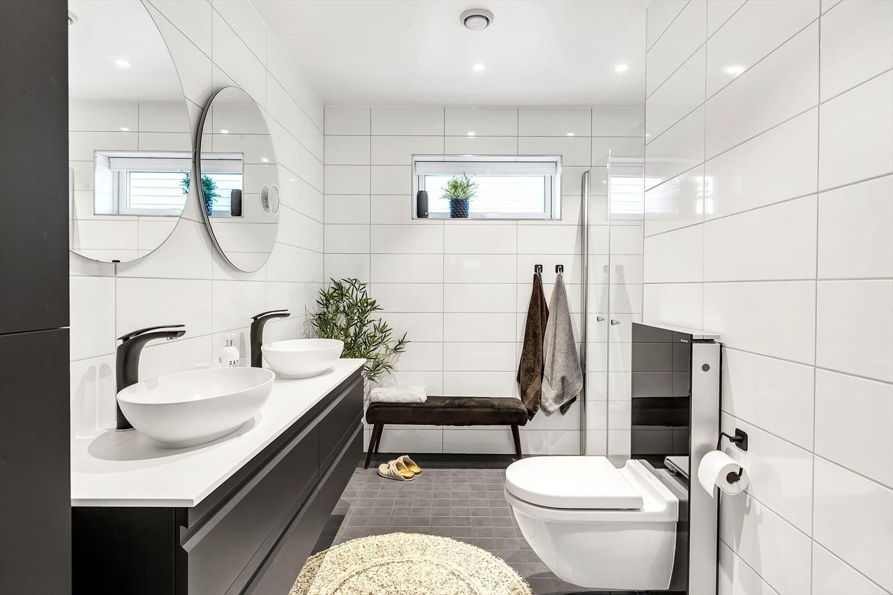 Hovedbadet er moderne og med pen innredning og speil med belysning. Dusjnisje. Vegghengt toalett.