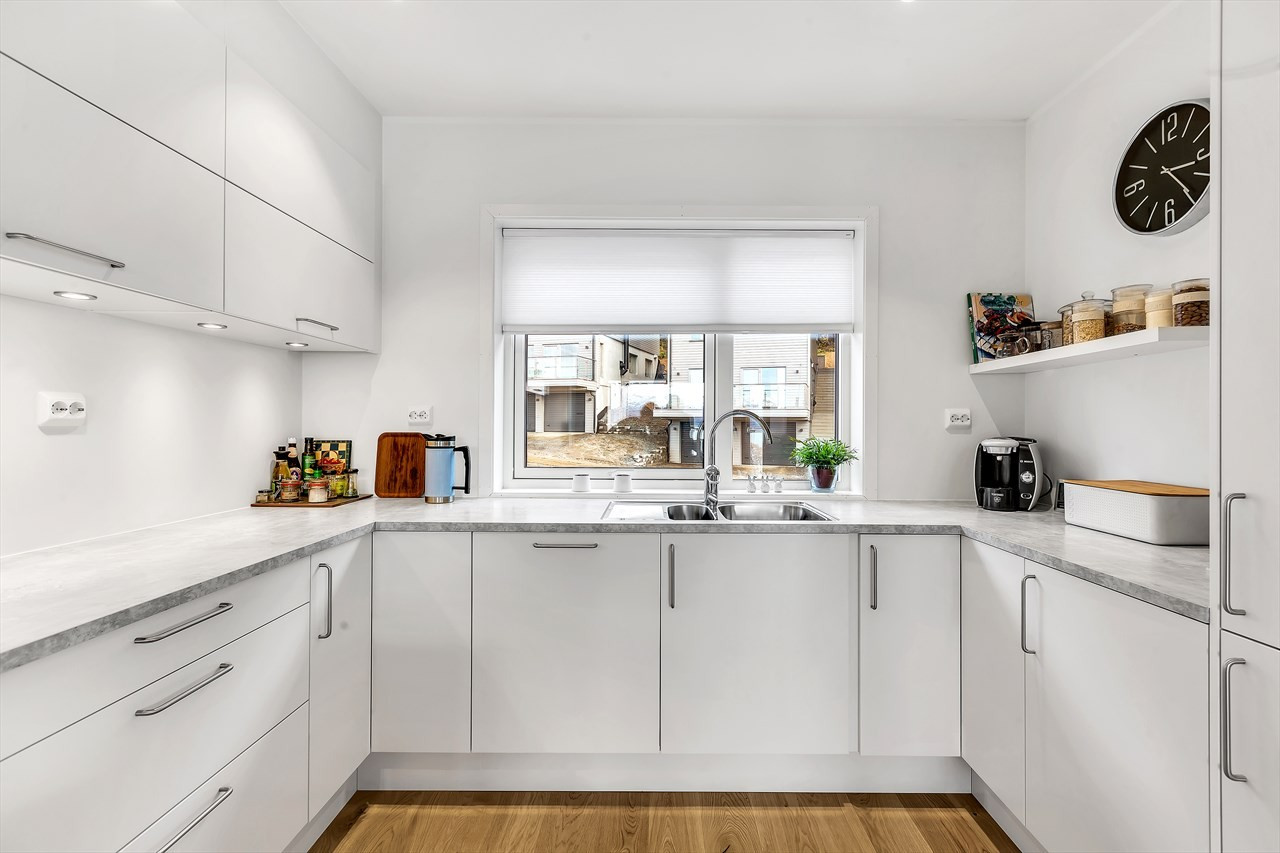 Innbydende og pent kjøkken med god benke- og oppbevaringsplass.