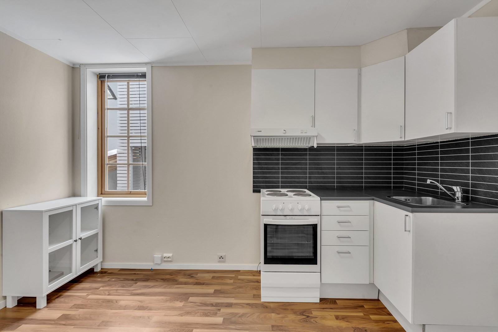 hjørnekjøkken med lyse fronter og kitchenboard bak benk.