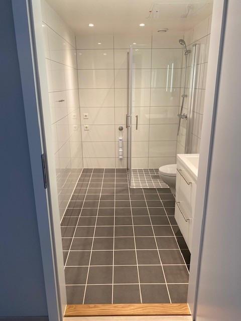Flott moderne bad med veggheng toalett og opplegg for vaskesøyle (vaskemaskin og tørketrommel).