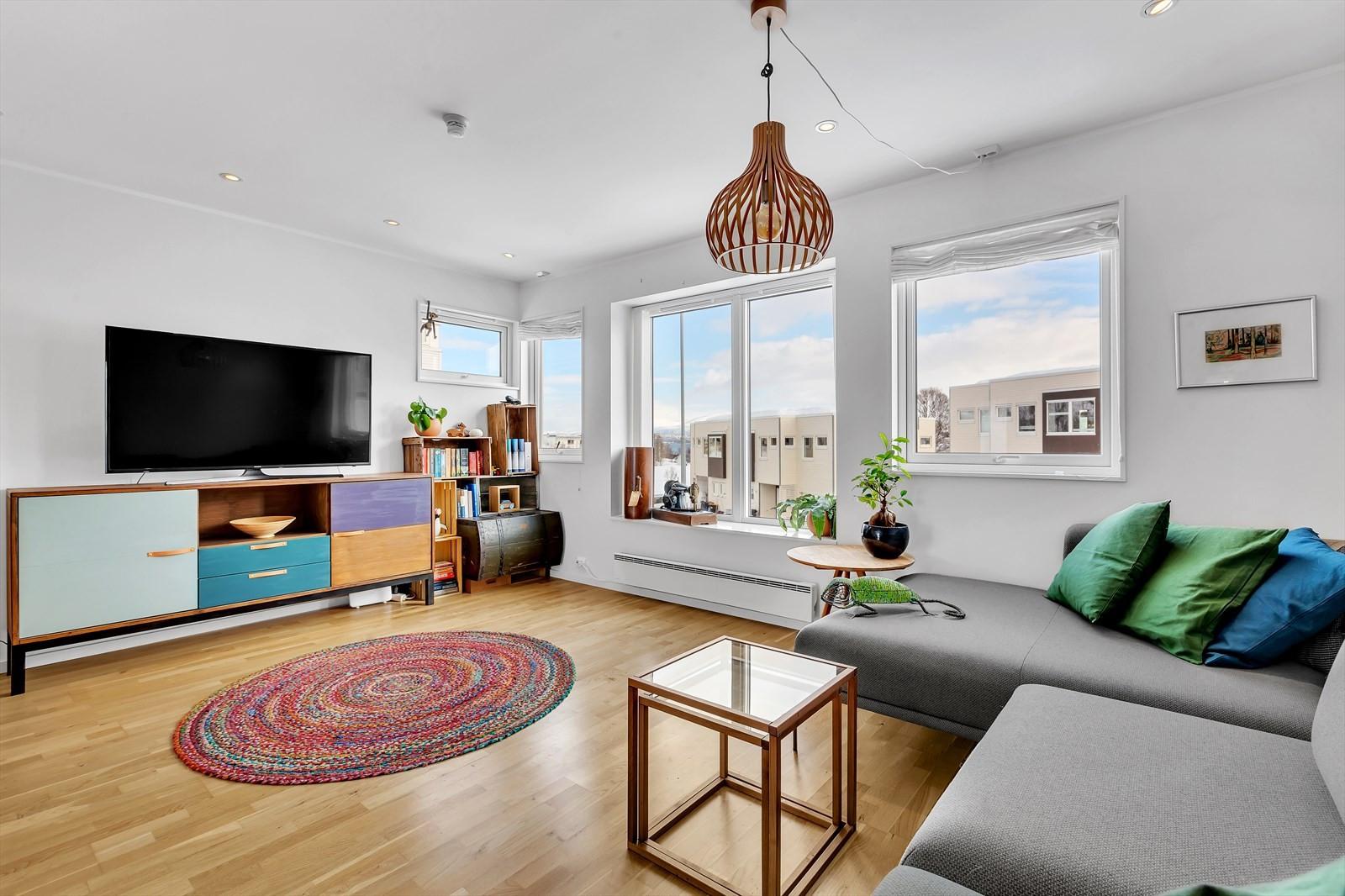 Lys og romslig stue i 2. plan med store vindusflater og himlingsbelysning.
