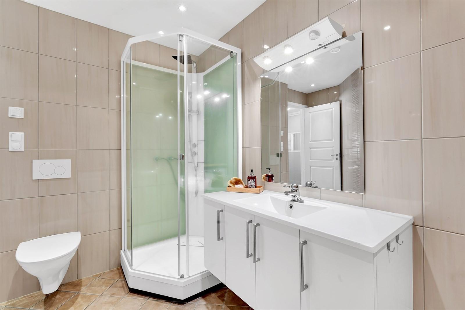 Badrom plan 1: Komplett flislagt med dusjkabinett, vegghengt toalett og opplegg vaskemaskin.