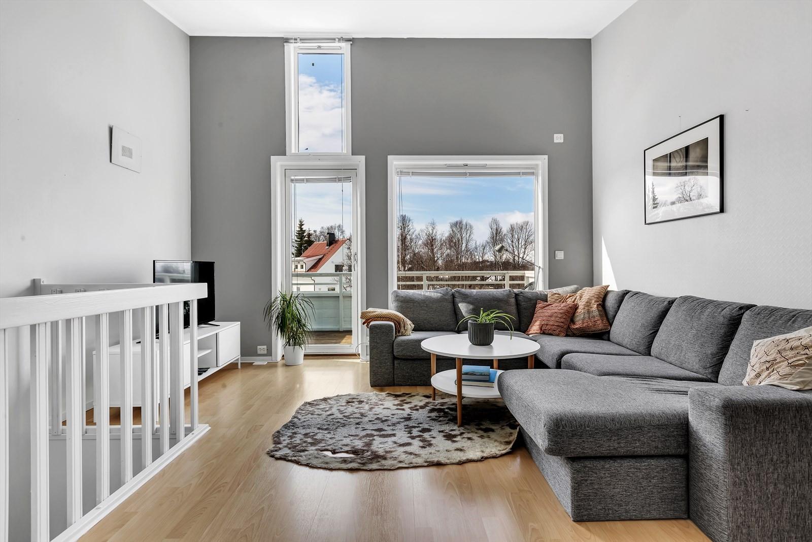 Leiligheten har en flott stue med stor takhøyde og fine vindusflater