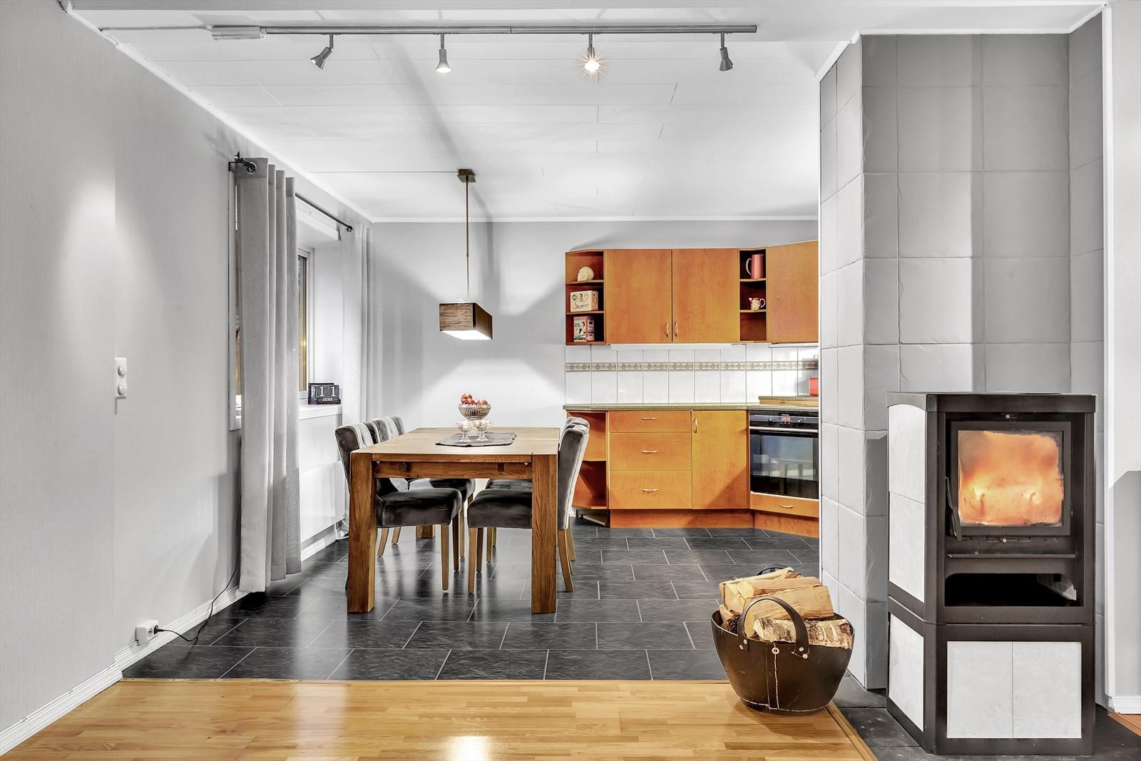 Delvis åpen løsning mellom stue og kjøkken. Effektiv og koselig vedovn skaper den rette hyggen