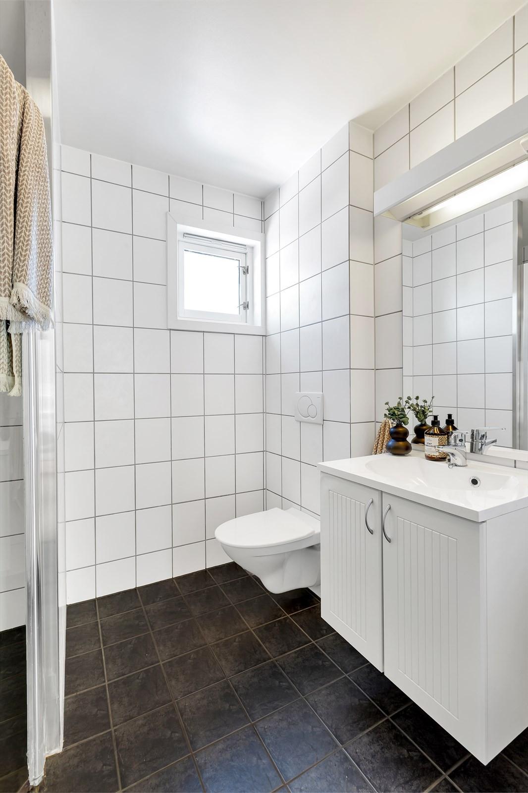 Vegghengt toalett og lyse innredninger med innfelt servant.