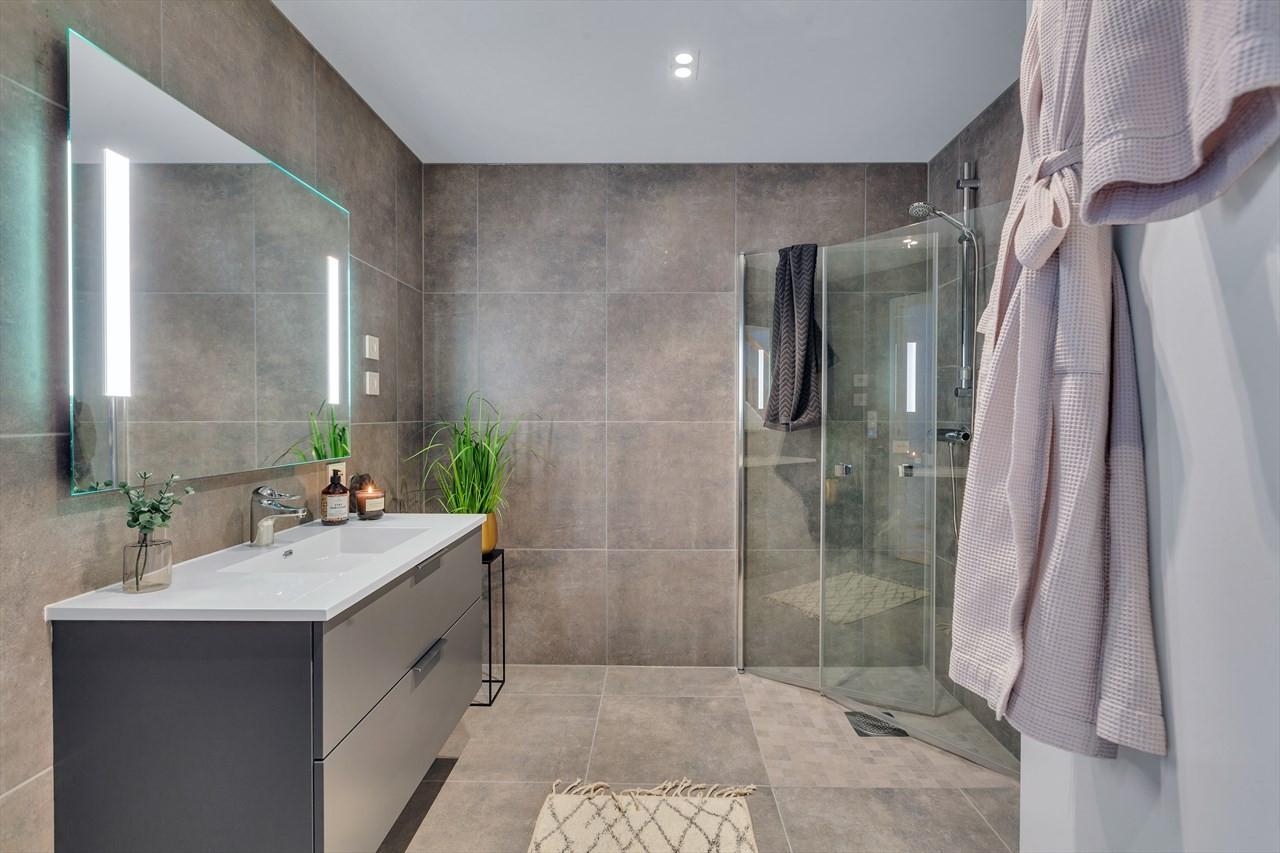 Boligene har to bad. Badene er flislagt med store fliser på vegg og gulv.