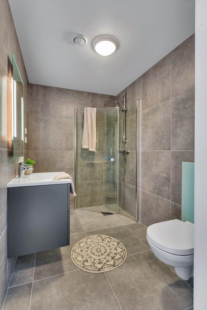 Flislagte bad med store moderne fliser, vegghengt toalett og dusjvegger.