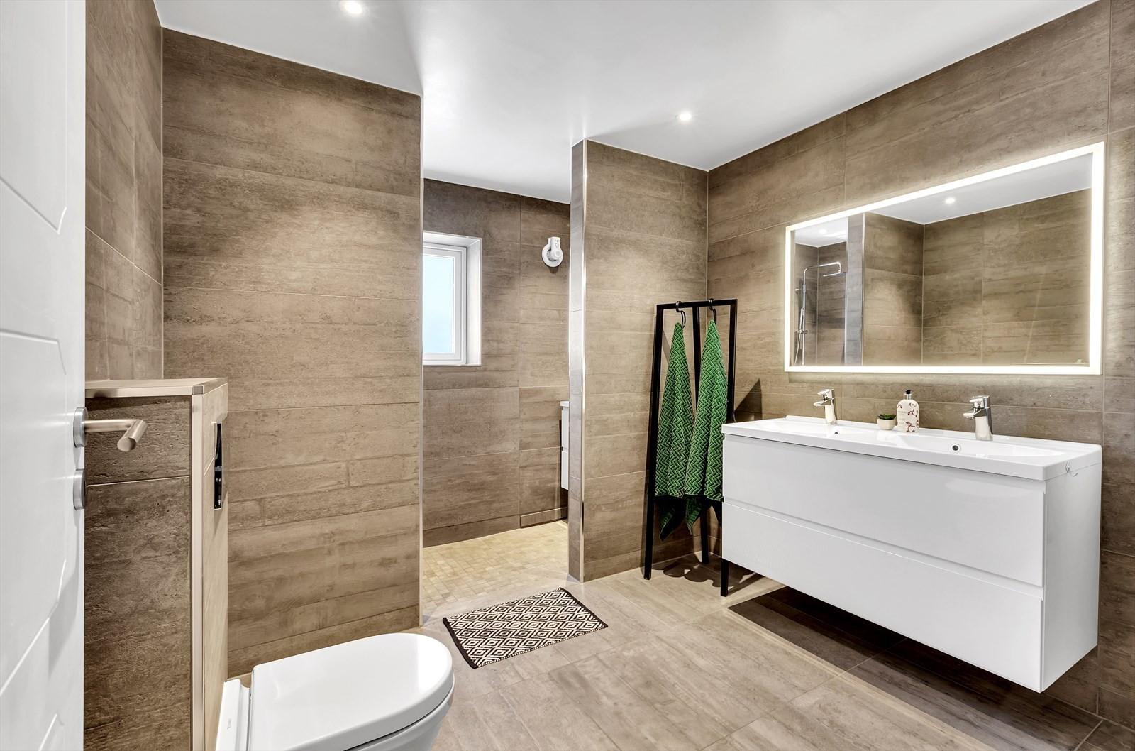 Boligen har ett meget delikat og stilrent bad med doble servanter, veggopphengt wc og romslig dusjhjørne.