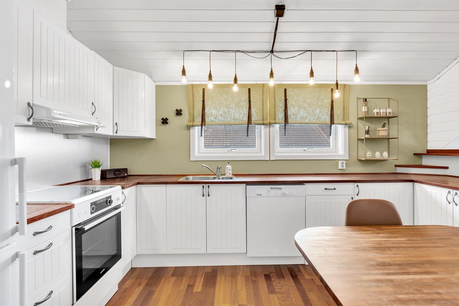 Delikat kjøkken med mye benkeplass og lysinnslipp fra vindu.