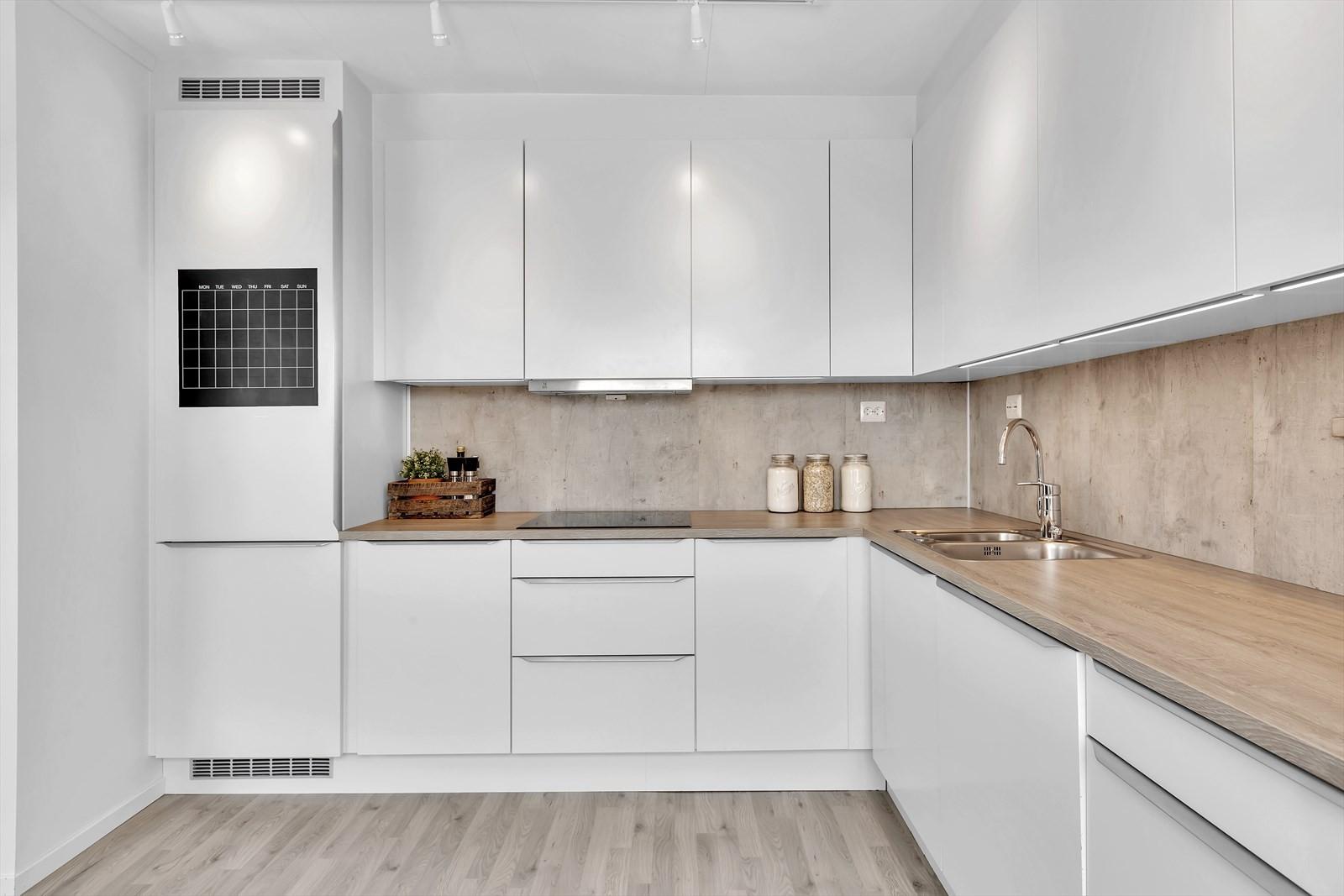 Moderne kjøkken med hvite fronter og integrerte hvitevarer