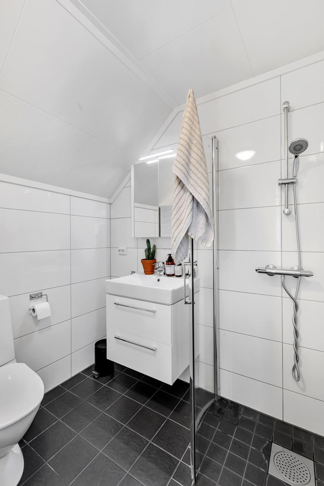 Flislagt bad på loftet med dusjhjørne og plass for vaskemaskin og tørketrommel.