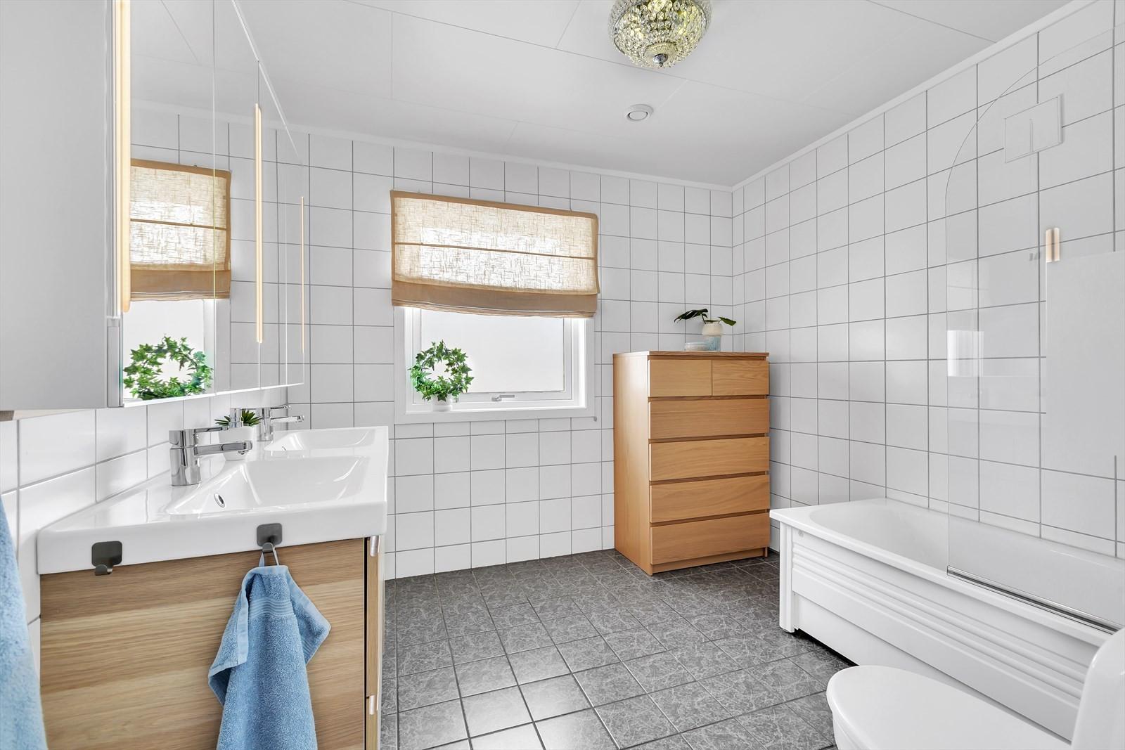 Badrom 1. etasje. Komplett flislagt, badekar med dusjløsning, toalett og moderne innredninger.