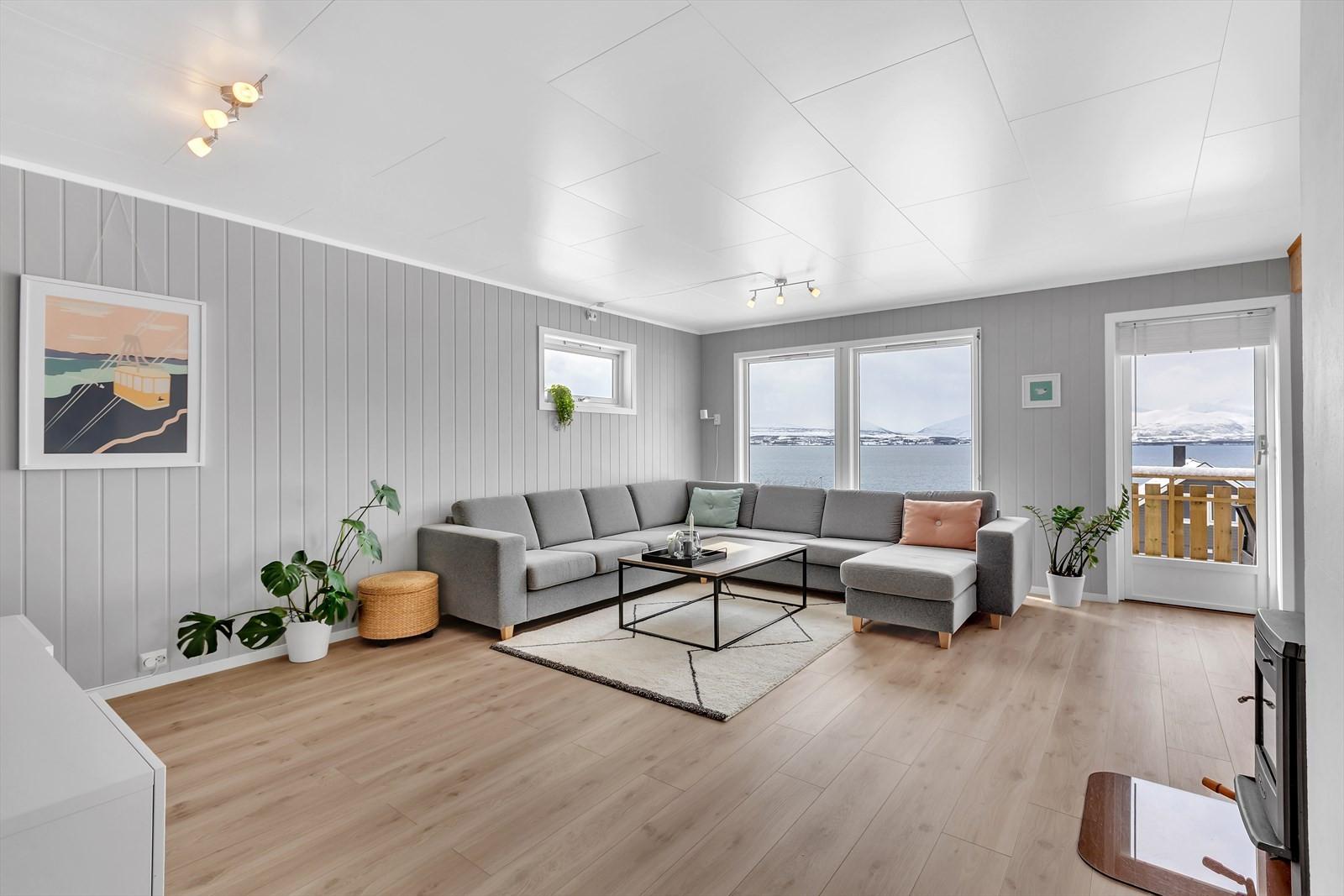 Lys og trivelig stue med tidsriktige fargevalg, en stavs gulv og nydelig utsikt.