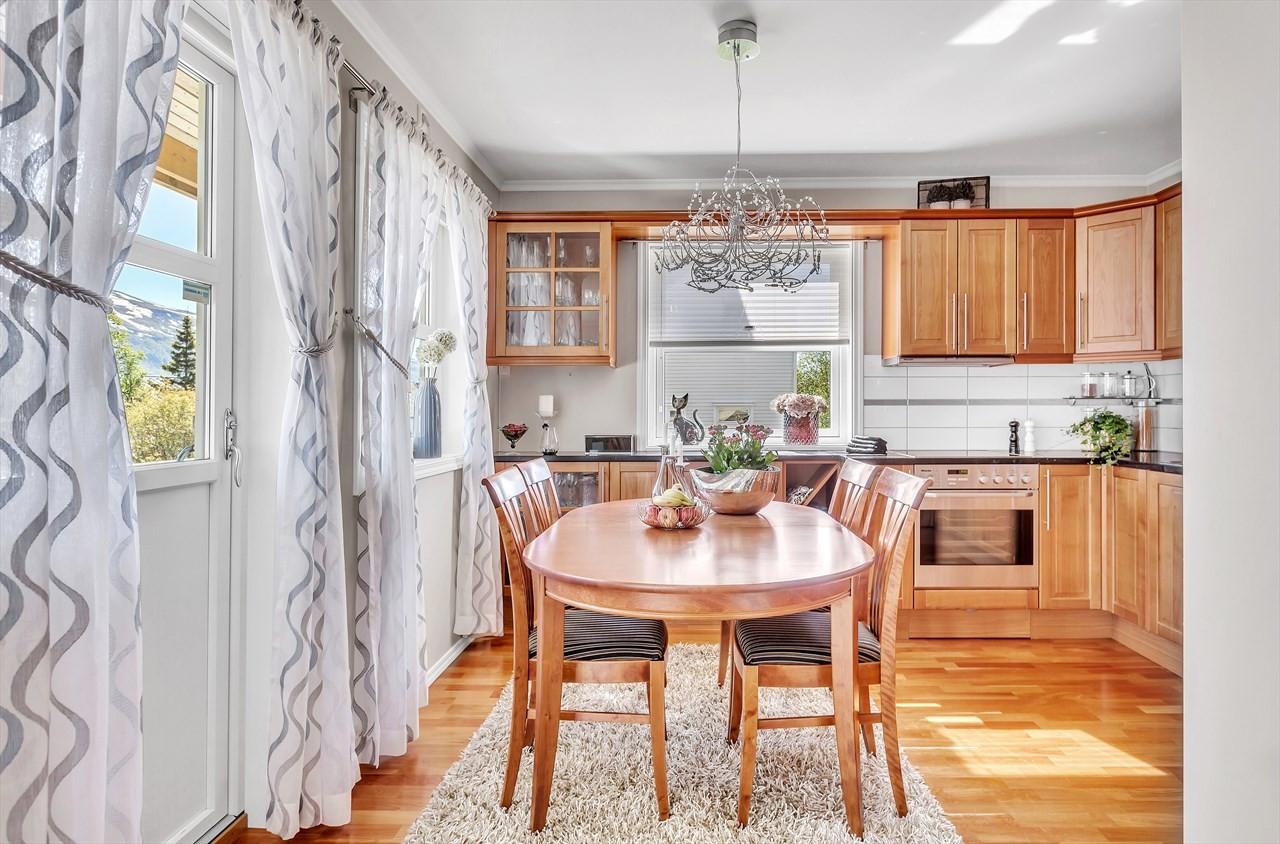 Påkostet kjøkken med integrerte hvitevarer og benkeplate i stein