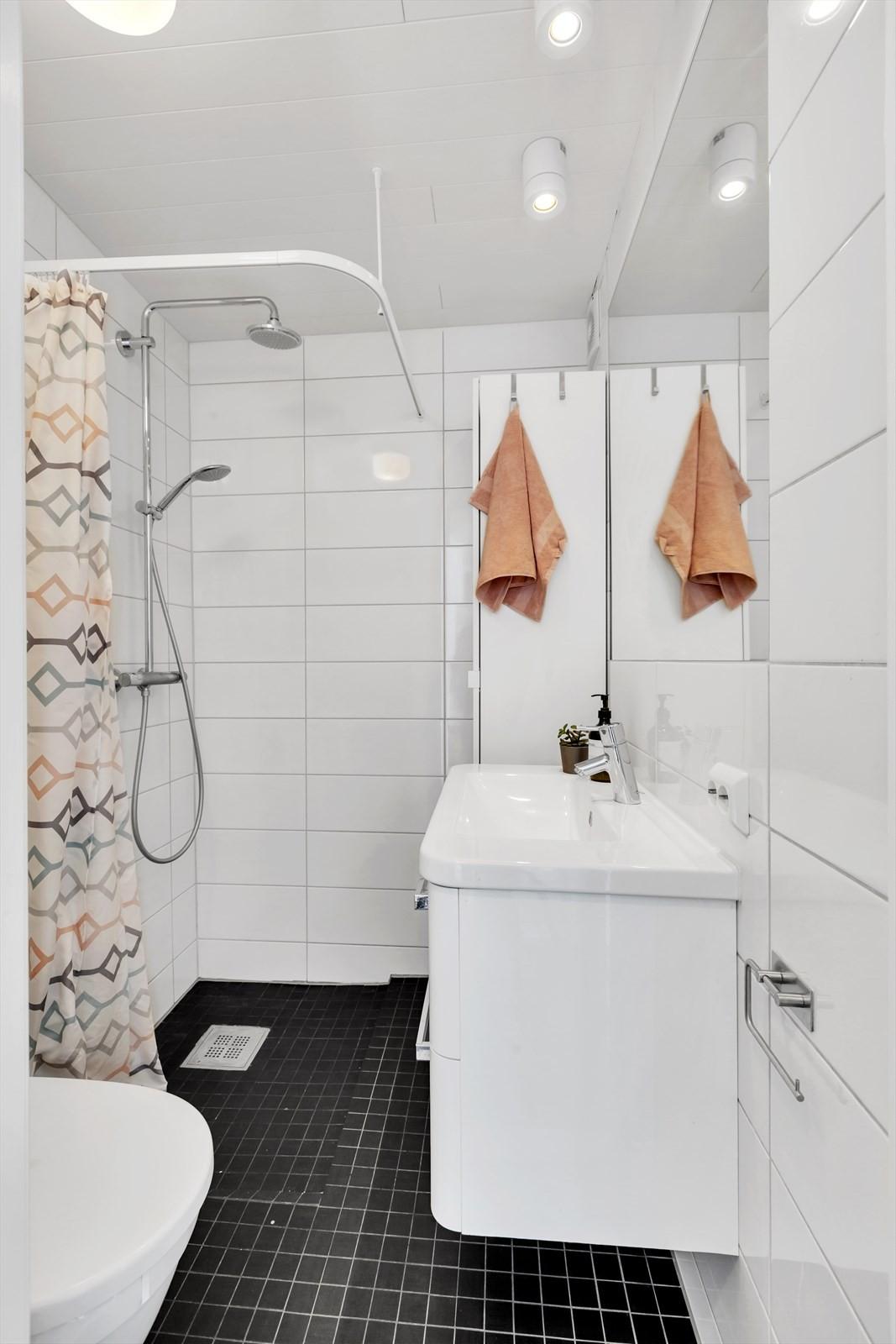 Badrom i 1. etasje, komplett flislagt med vegghengt toalett og dusjnisje.