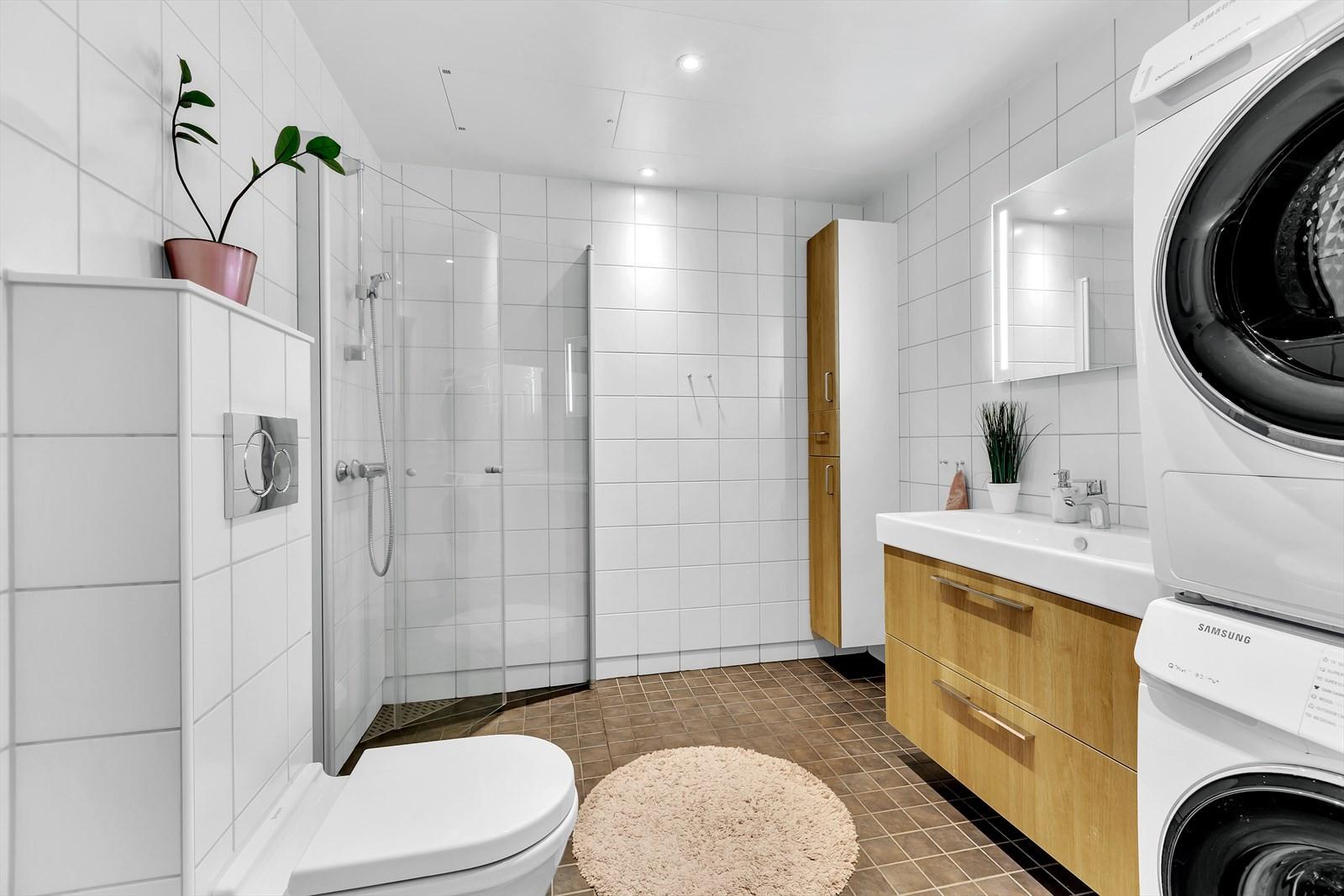 Badet er flislagt på gulv og vegger. Plassering er  mellom soverommene