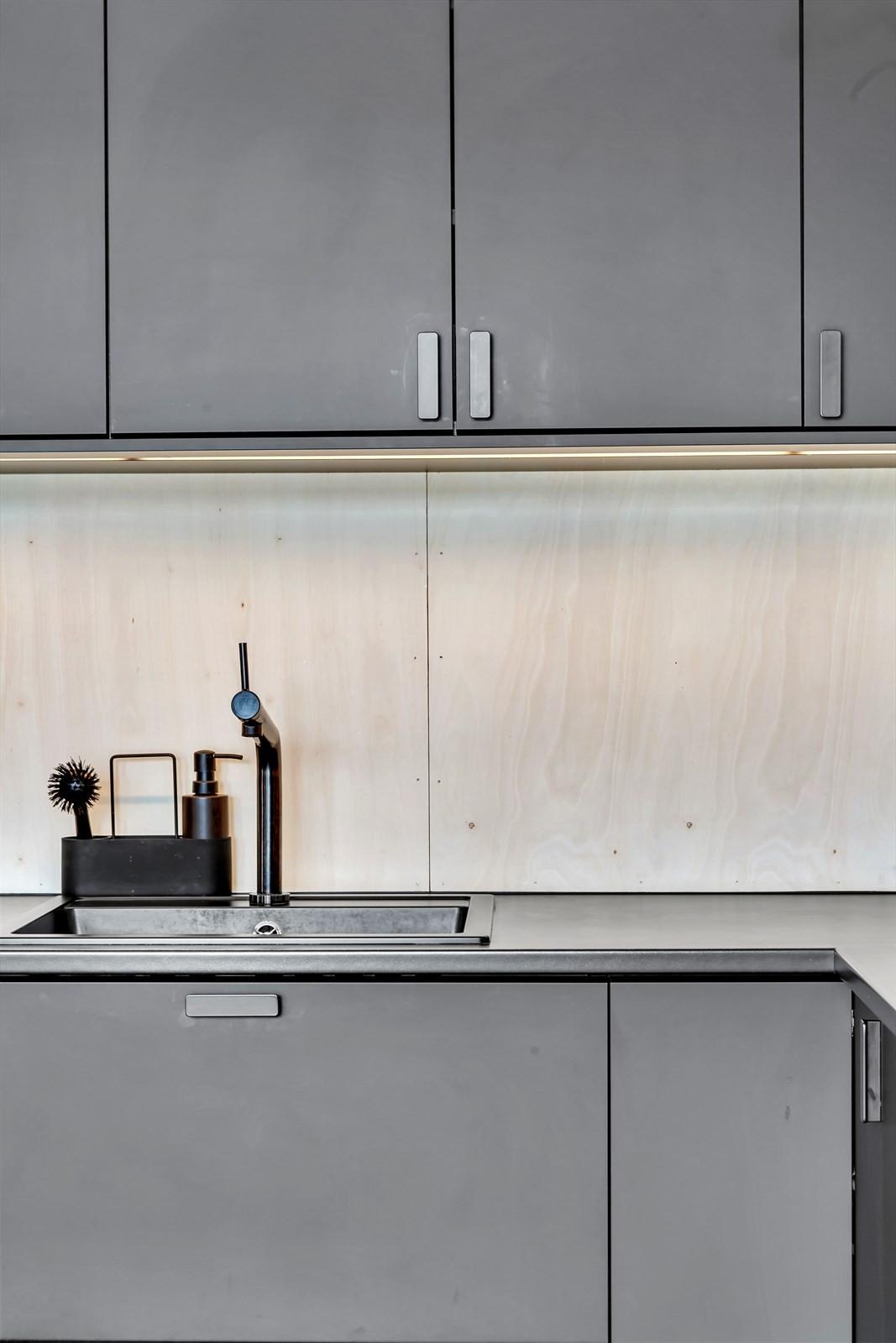 Lekkert kjøkken med finêrplater over kjøkkenbenken