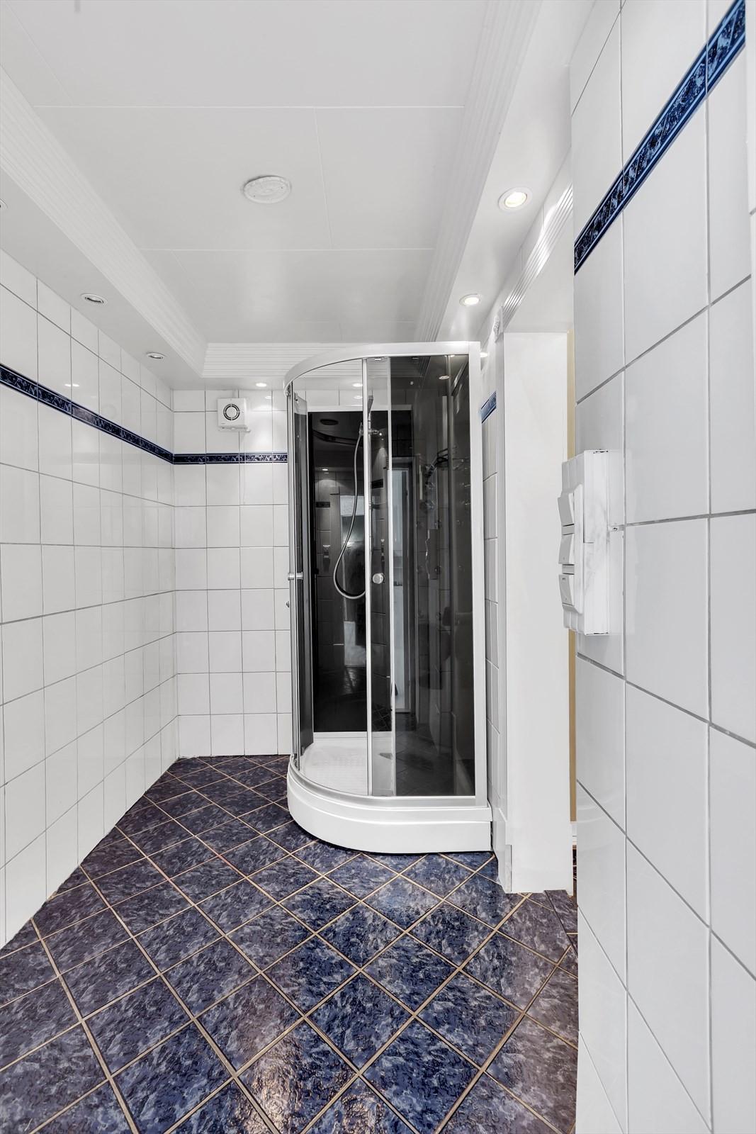 Flislagt bad med dusjkabinett, servant med skap og wc.