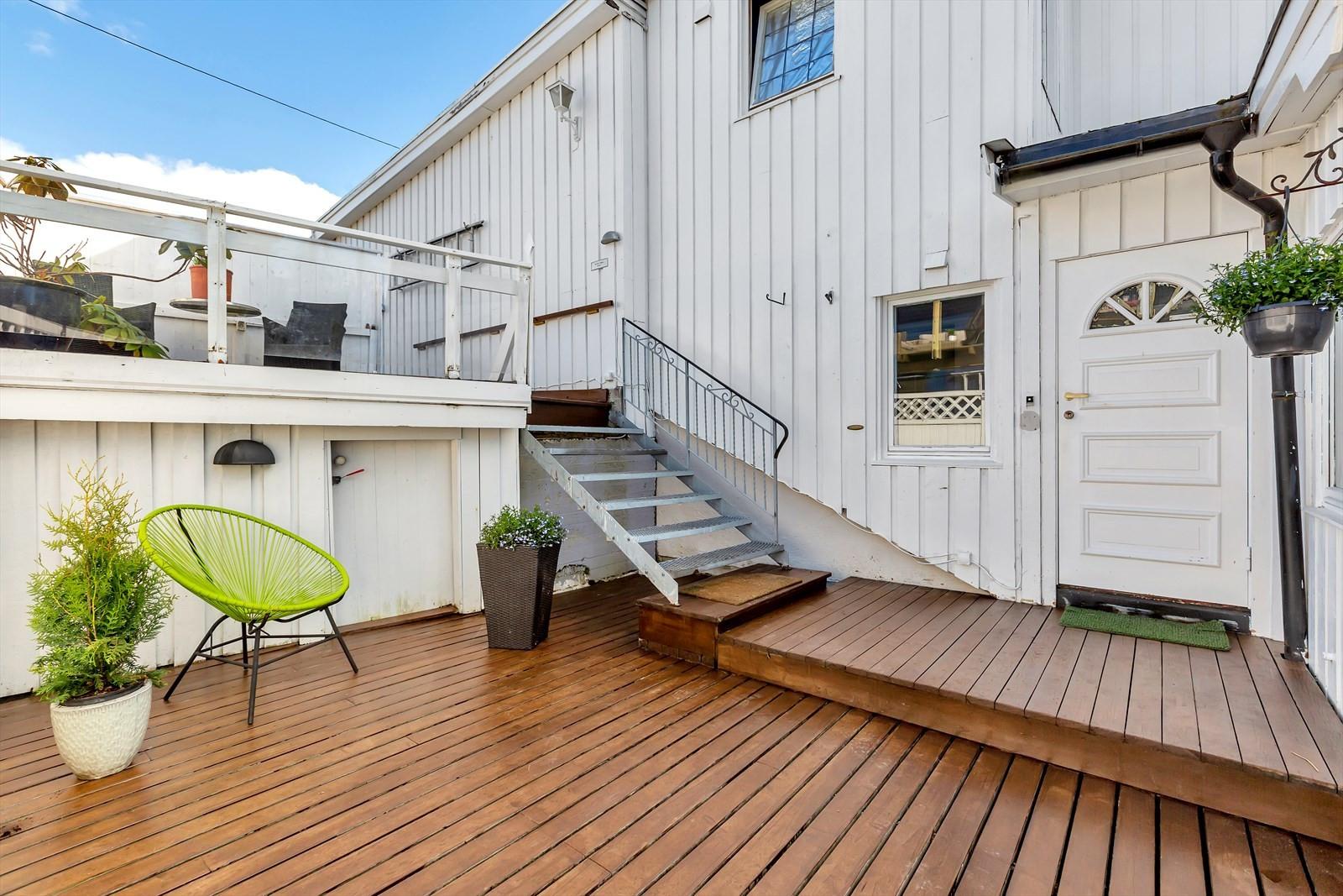 Meget innbydende inngangsparti og en solrik og romslig terrasse og platting rett utenfor boligen.