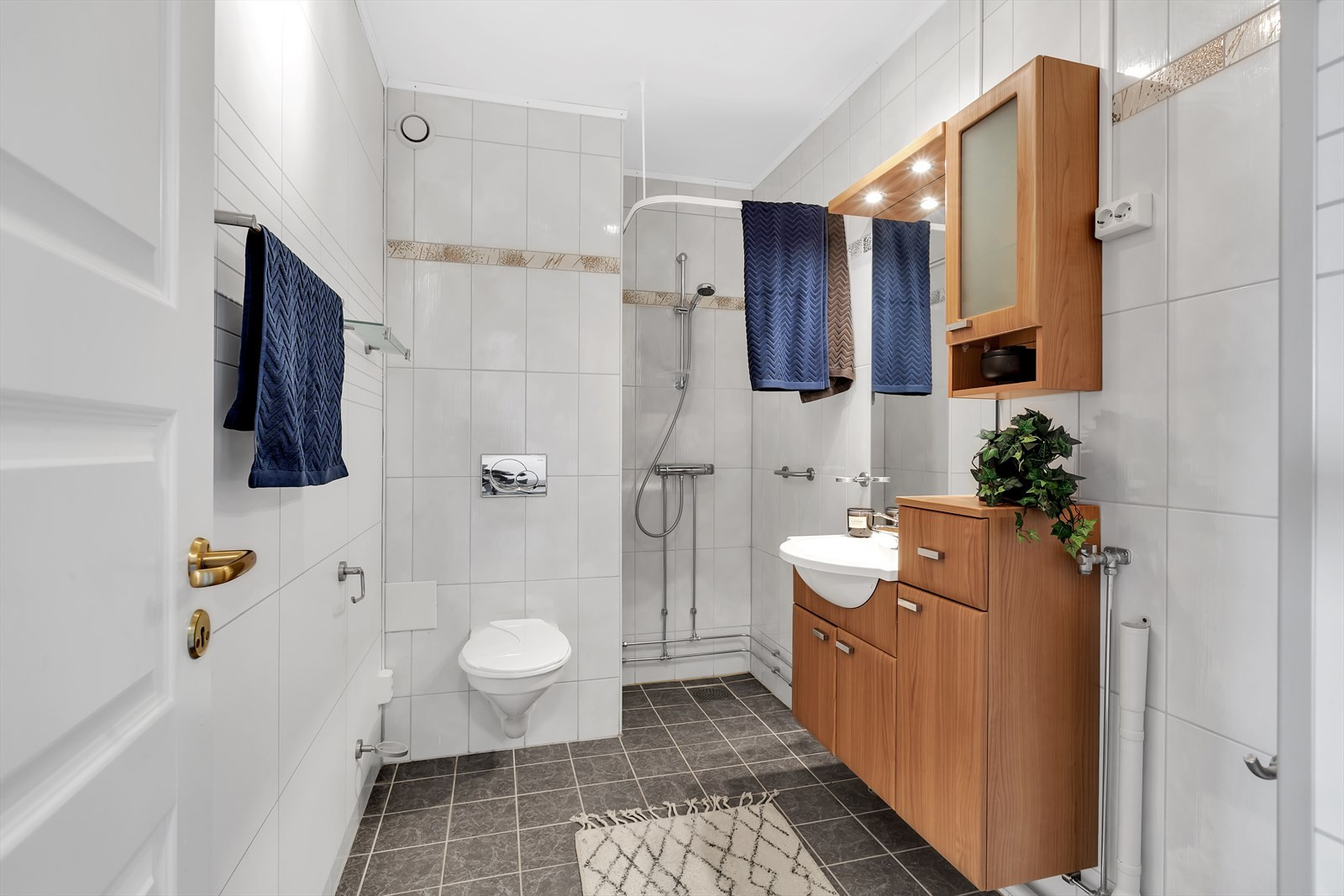 Flislagt badrom med vegghengt toalett.