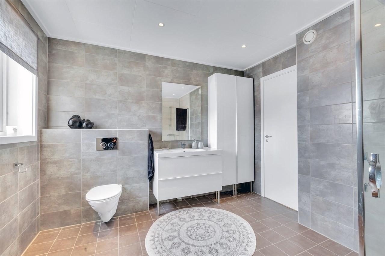 Komplett flislagt badrom m/ vegghengt toalett, moderne innredninger og dusjhjørne.