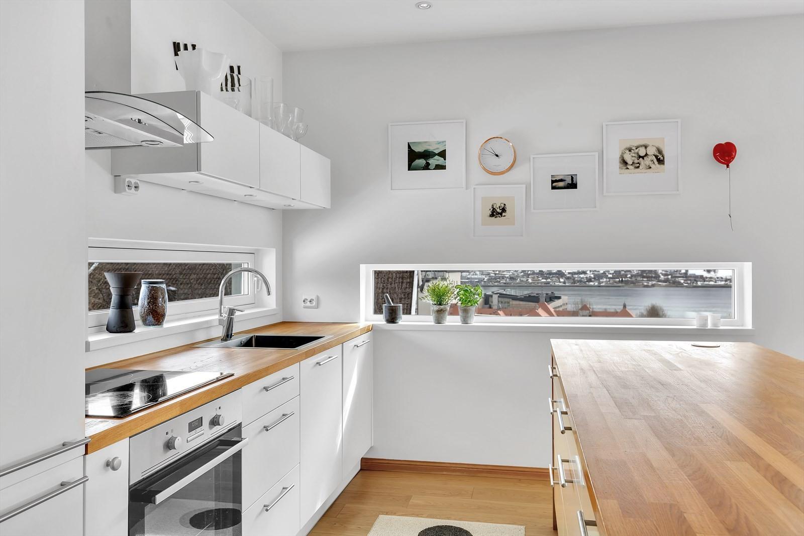 Kjøkkenet er moderne utførelse med slette hvite fronter og benkeplate i tre