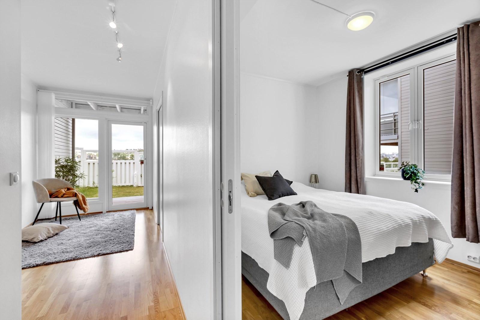 Soverom og mellomgang med store vindusflater og utgang til vestvendt markplatt.