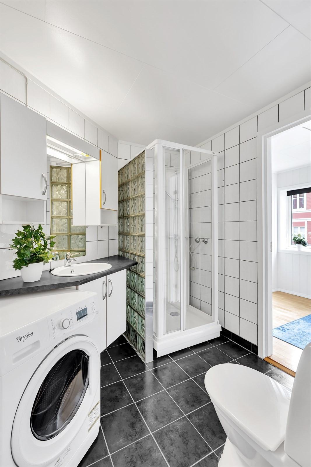 Flislagt bad med duskabinett, opplegg til vaskemaskin, wc og servant.