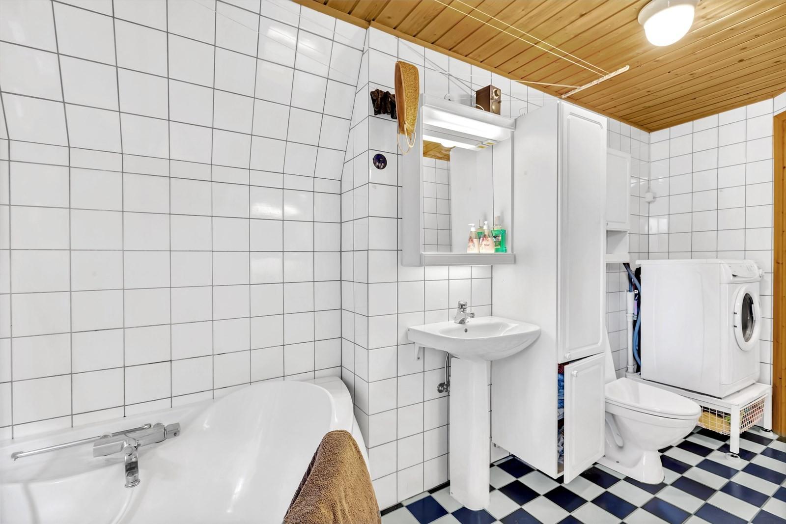Flislagt bad i plan 1 badekar, servant med speil, wc og opplegg til vaskemaskin.