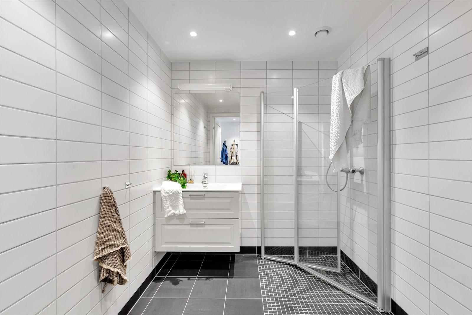 Komplett flislagt bad. Mosaikkfliser i dusjsone. Innslagbare dusjdøærer i herdet glass. Downlights i taket. Vegghengt toalett.