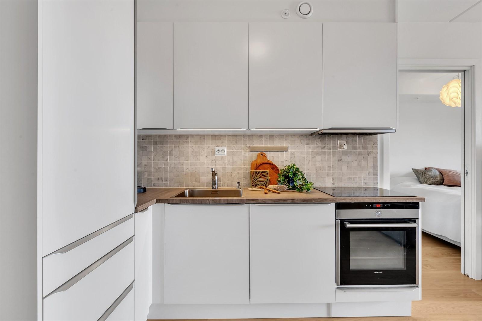 Innbydende og moderne kjøkken med integrerte hvitevarer.