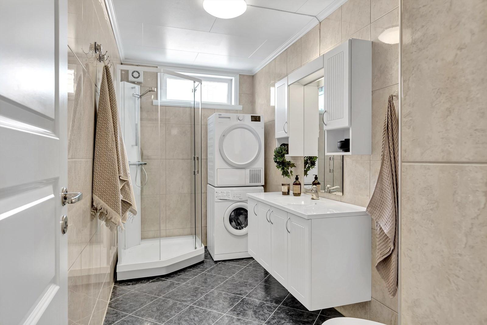 Komplett flislagt badrom med dusjkabinett, romslige innredninger, opplegg vaskesøyle og toalett.
