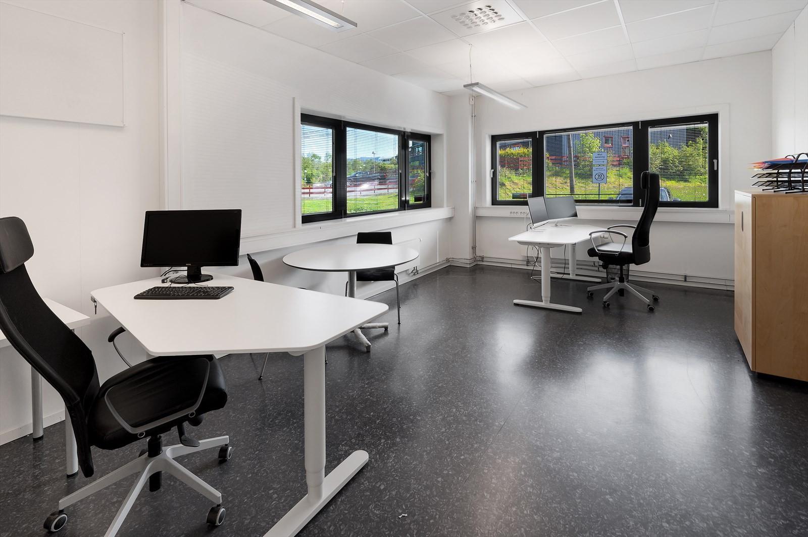 Åpent kontorlandskap i hjørnet av lokalet.