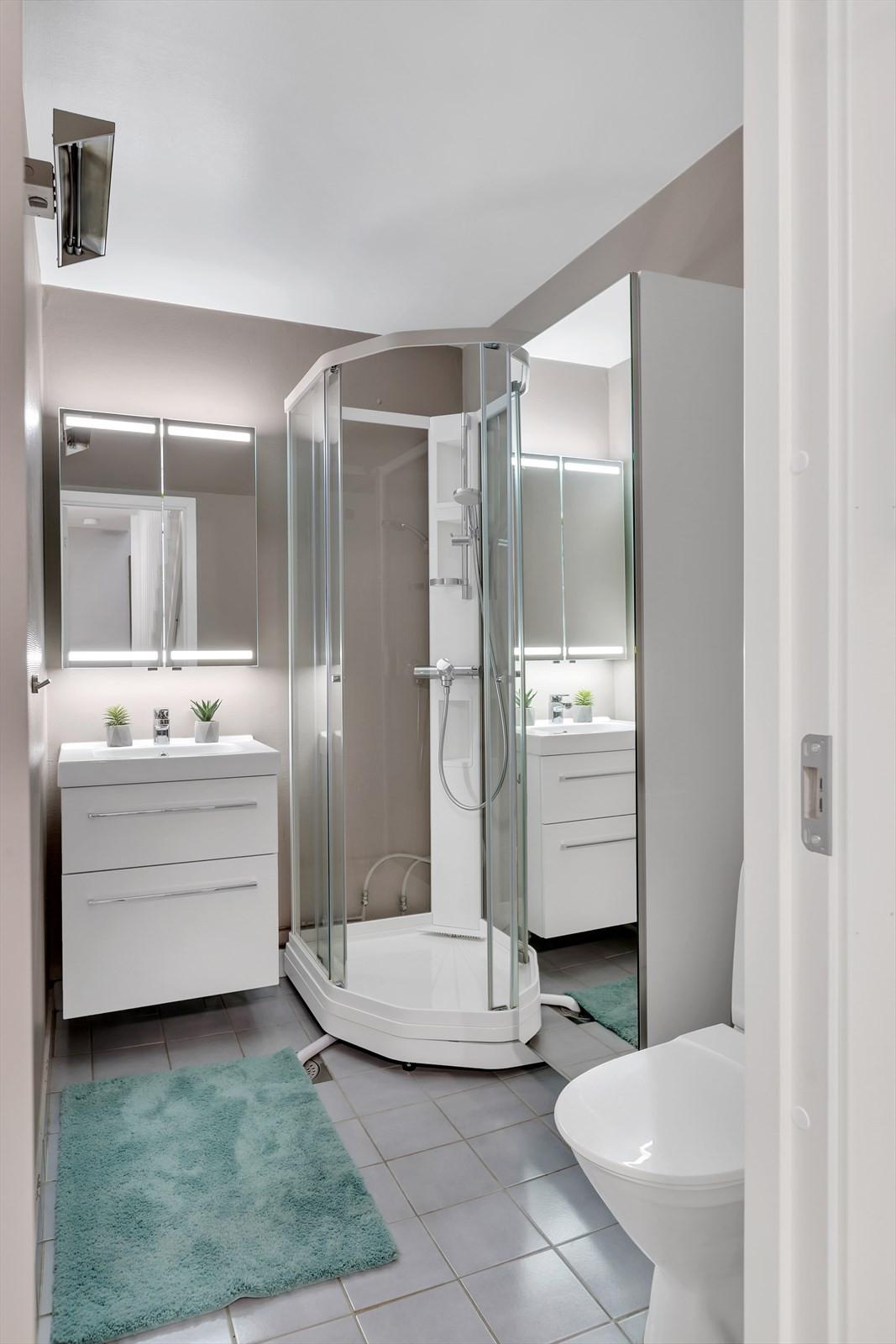 Bad med fliser på gulv. Nyere WC. Dusjkabinett.