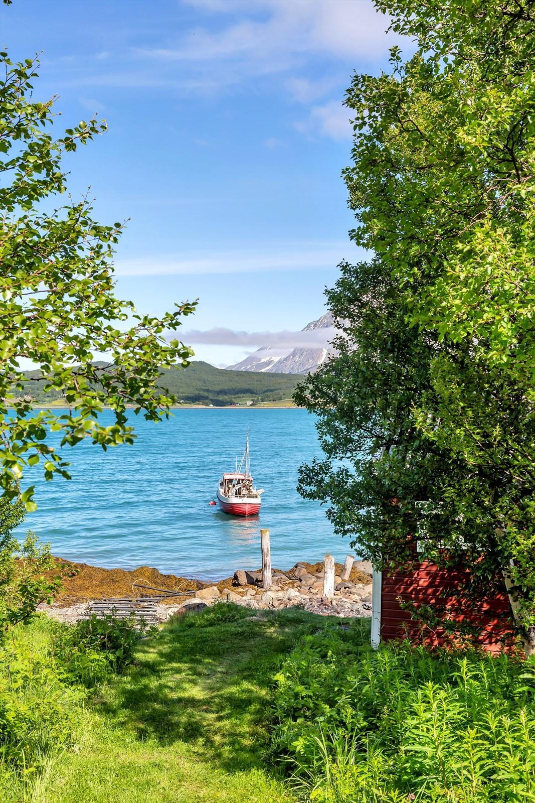 Utsikt fra tomten. Båtstø til venstre for naustet.