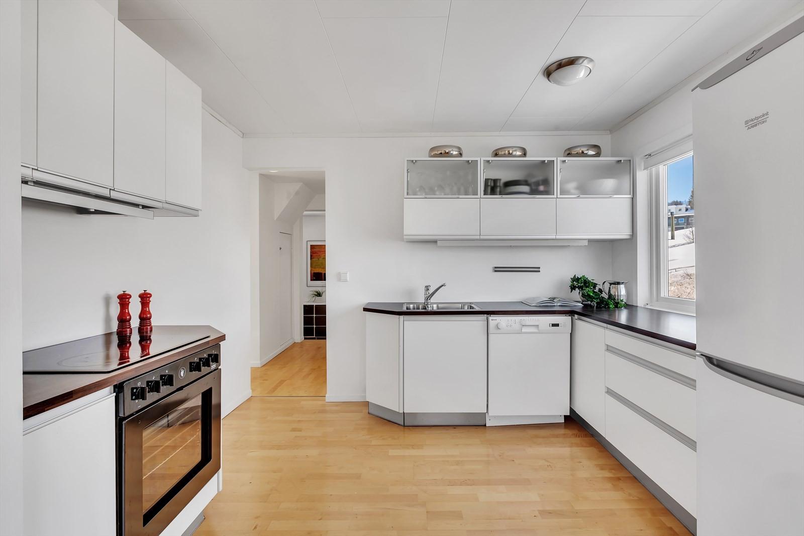 Kjøkken har lyse innredninger og  godt med benkeplass.