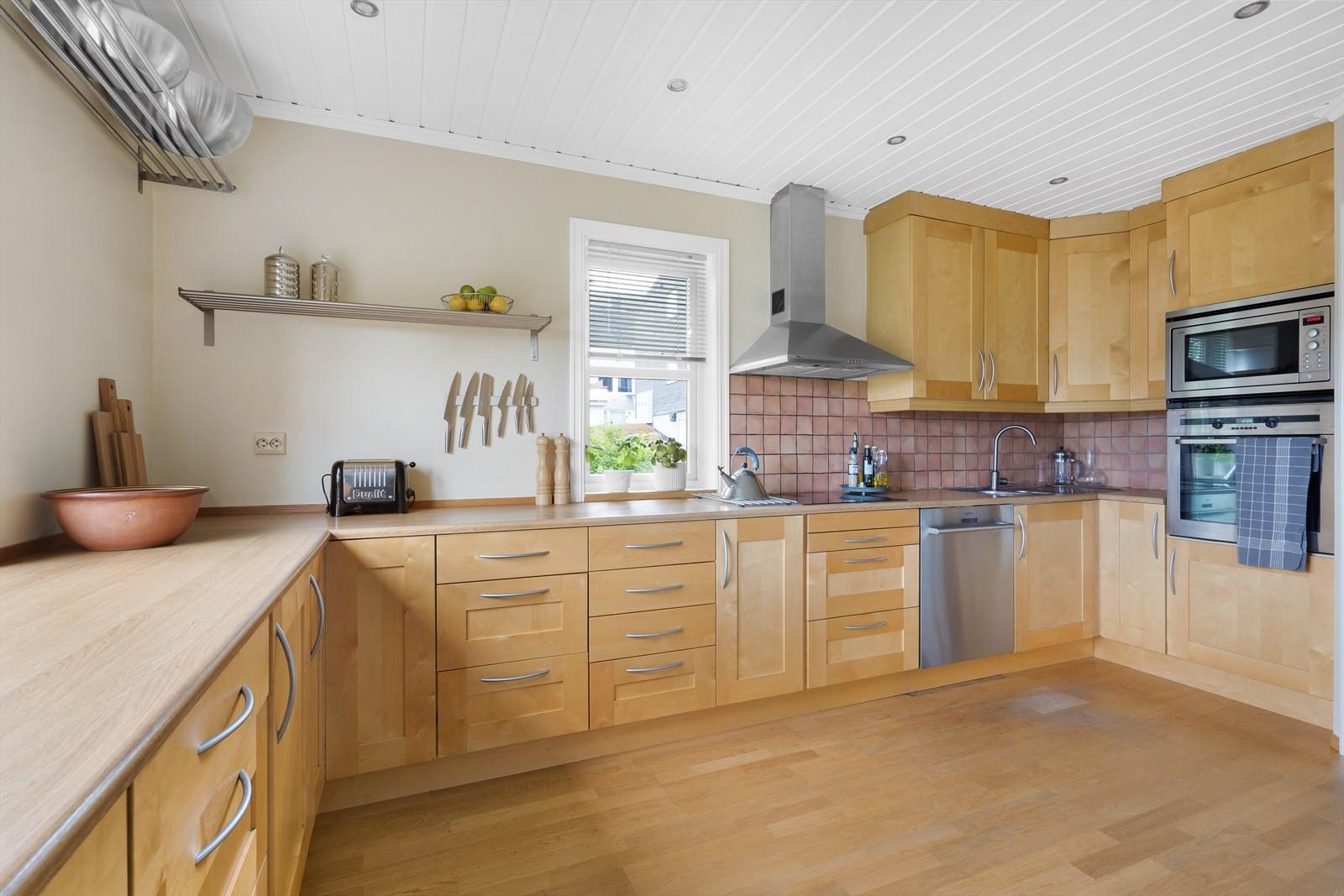 KJøkkenet er stort og innholdsrikt med integrerte hvitevarer og rikelig med benkeplass