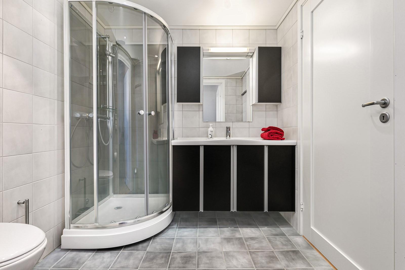 Flislagt badrom med moderne innredninger.