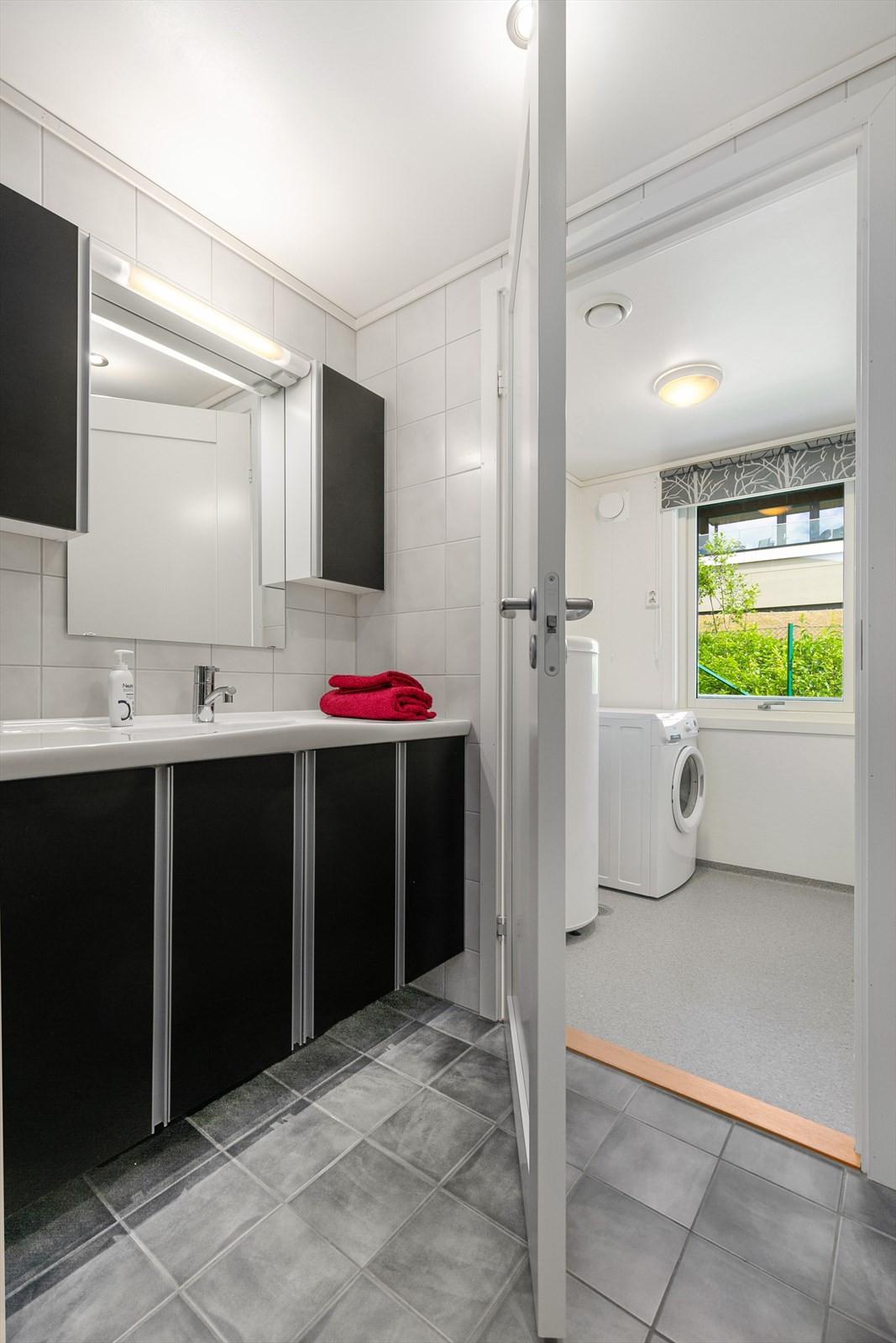 Flislagt badrom med vaskerom tilknyttet.