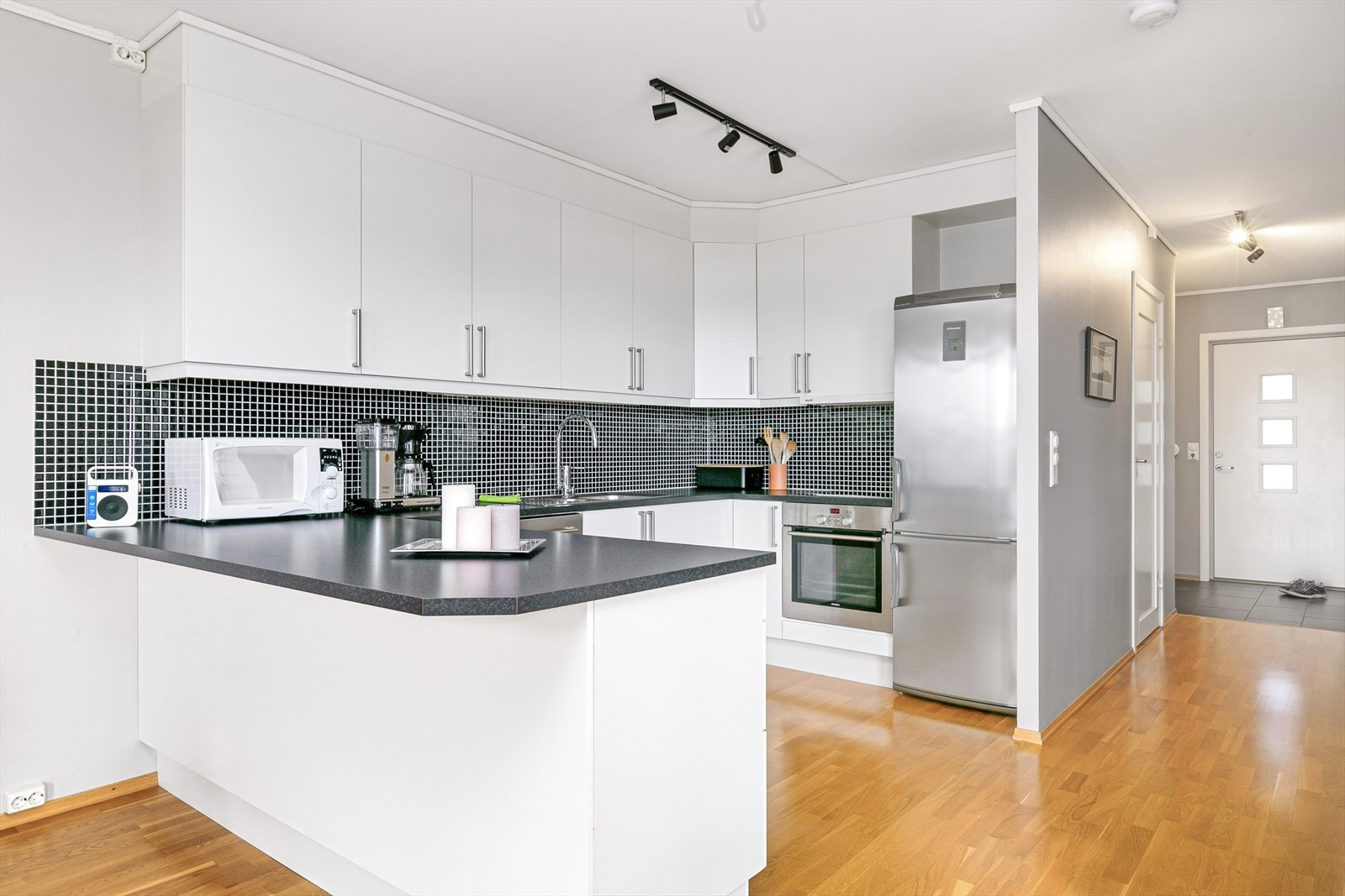 Åpen, moderne kjøkkenløsning med ekstra god benkeplass.