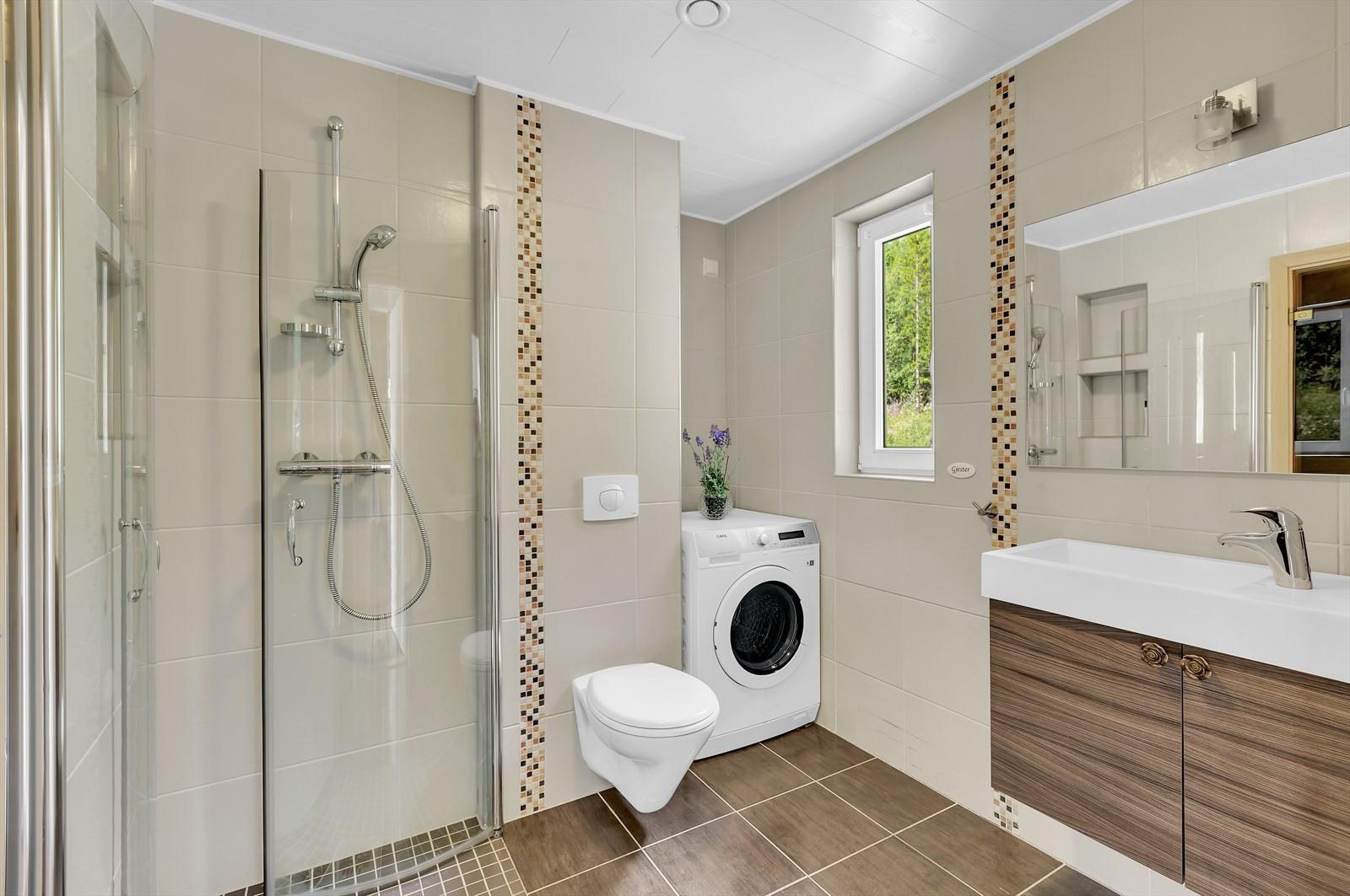 Boligen har et strøkent bad. Flislagt bad med dusjhjørne, veggopphengt toalett, servant med over og underskap.
