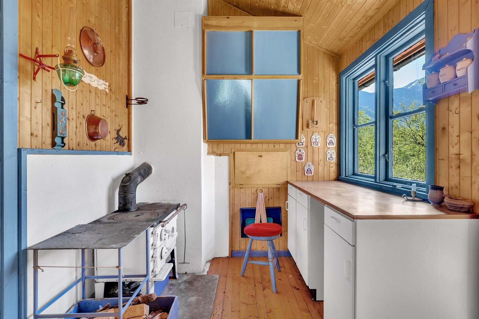 Kjøkken med vedovn og enkel kjøkkeninnredning