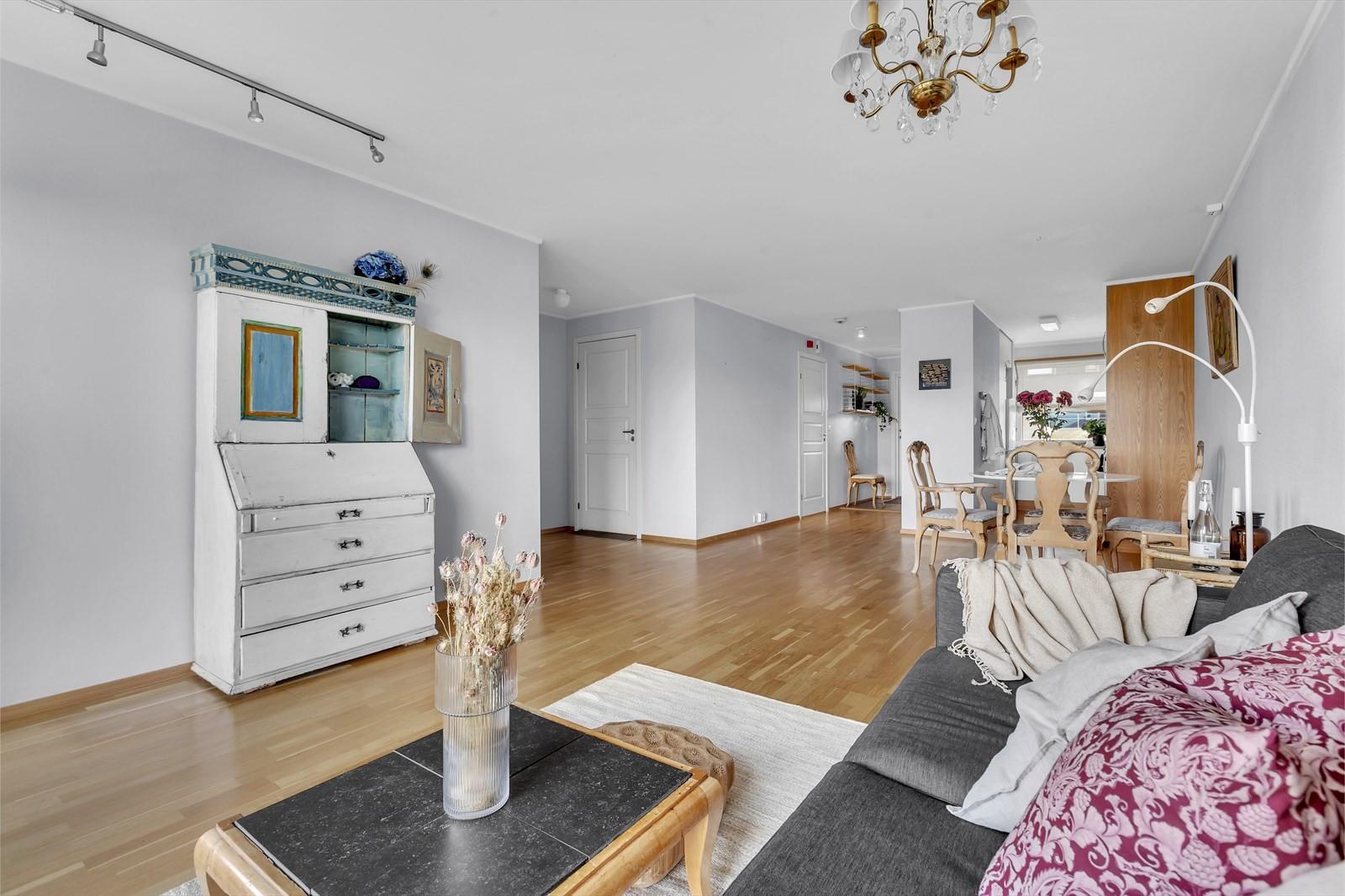 Stor stue med delvis åpen løsning mot kjøkkenet