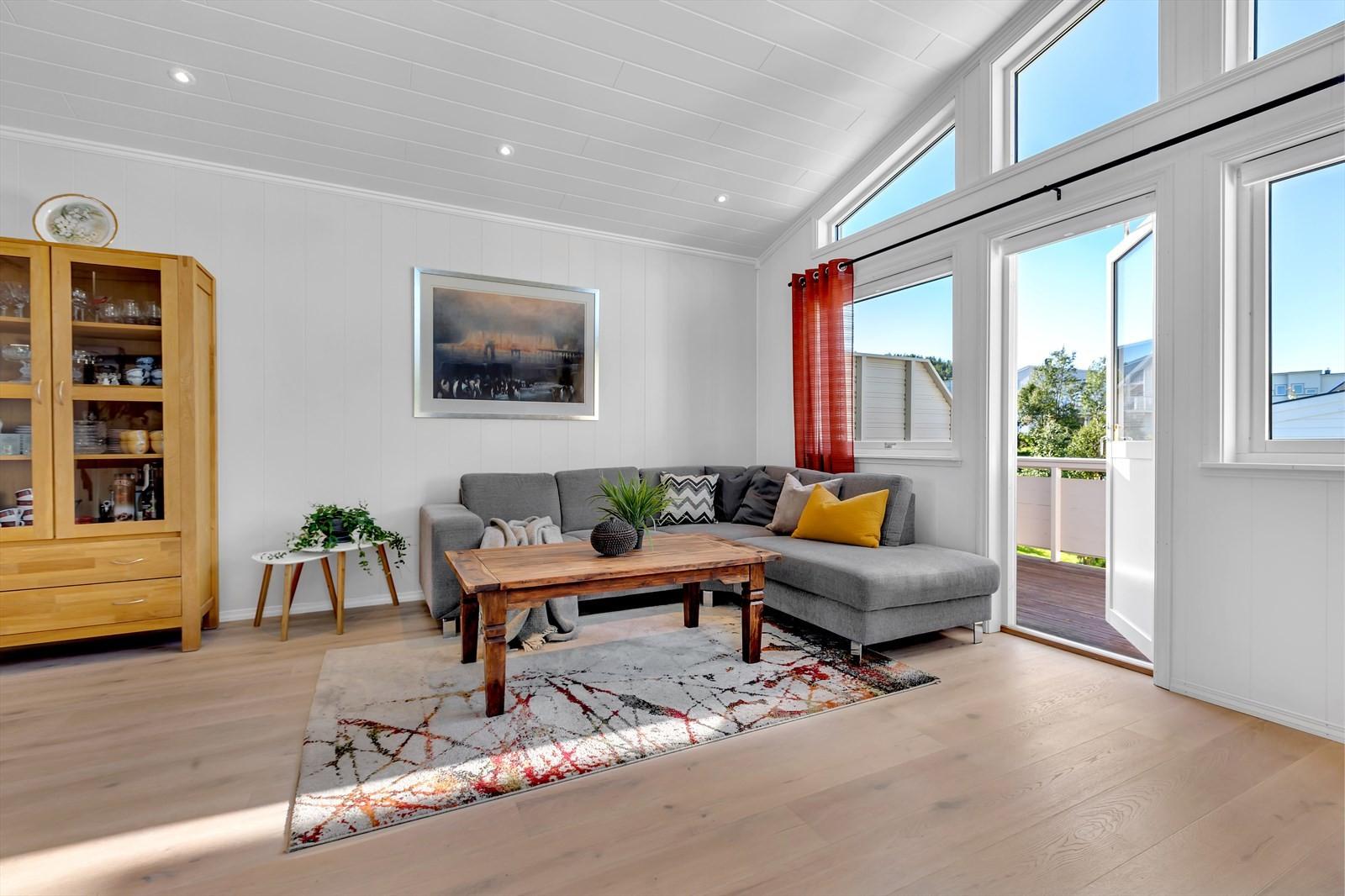 Lys og stor stue med store vinduer. Utgang til vestvendt veranda